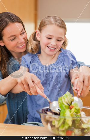 Portrait of a mother preparing a salad with her daughter stock photo, Portrait of a mother preparing a salad with her daughter in a kitchen by Wavebreak Media