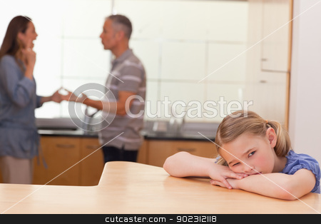 Sad girl hearing her parents fitting stock photo, Sad girl hearing her parents fitting in a kitchen by Wavebreak Media