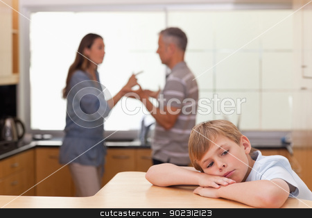 Sad little boy hearing his parents arguing stock photo, Sad little boy hearing his parents arguing in a kitchen by Wavebreak Media