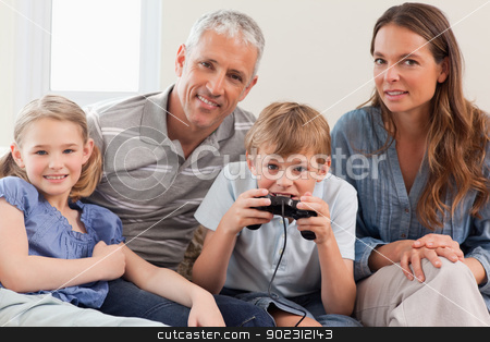 Charming family playing video games stock photo, Charming family playing video games in a living room by Wavebreak Media
