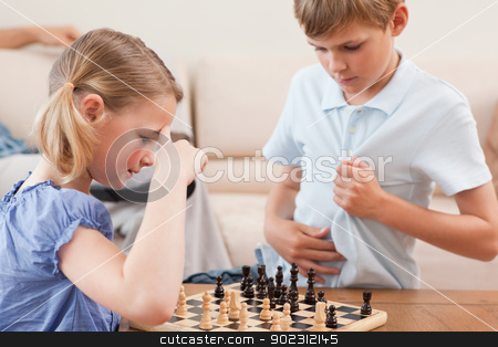 Siblings playing chess stock photo, Siblings playing chess in a living room by Wavebreak Media