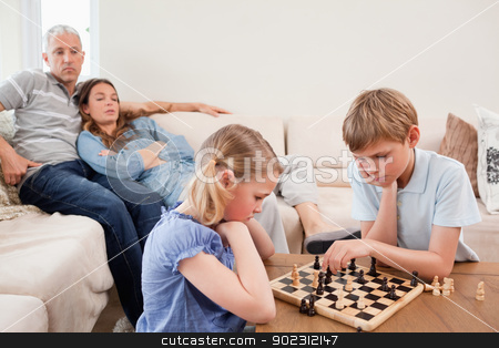 Siblings playing chess in front of their parents stock photo, Siblings playing chess in front of their parents in a living room by Wavebreak Media