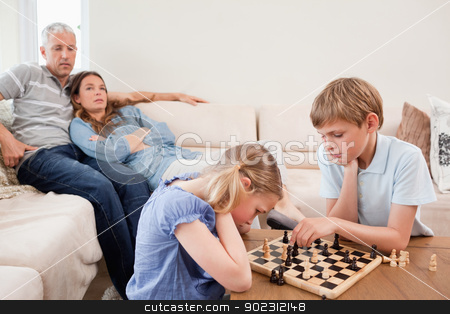 Children playing chess in front of their parents stock photo, Children playing chess in front of their parents in a living room by Wavebreak Media