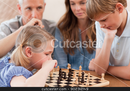 Focused children playing chess in front of their parents stock photo, Focused children playing chess in front of their parents in a living room by Wavebreak Media