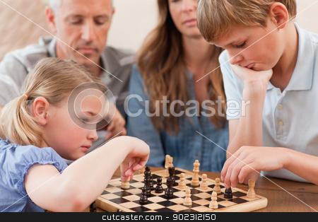 Focused siblings playing chess in front of their parents stock photo, Focused siblings playing chess in front of their parents in a living room by Wavebreak Media