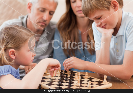 Close up of siblings playing chess in front of their parents stock photo, Close up of siblings playing chess in front of their parents in a living room by Wavebreak Media