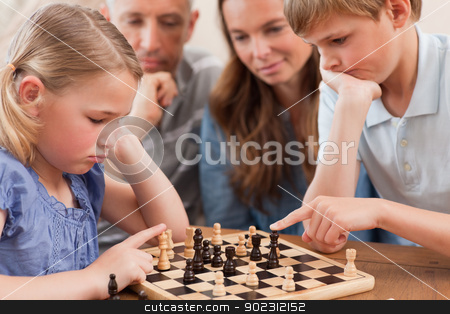 Close up of children playing chess in front of their parents stock photo, Close up of children playing chess in front of their parents in a living room by Wavebreak Media
