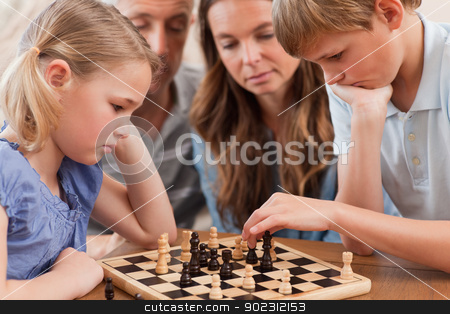 Close up of serious children playing chess in front of their par stock photo, Close up of serious children playing chess in front of their parents in a living room by Wavebreak Media