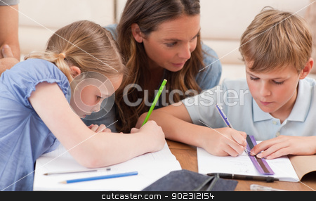 Mother helping her children to do their homework stock photo, Mother helping her children to do their homework in a living room by Wavebreak Media
