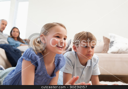 Children playing video games while their parents are watching stock photo, Children playing video games while their parents are watching in a living room by Wavebreak Media
