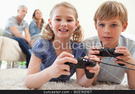 Playful siblings playing video games with their parents on the b stock photo, Playful siblings playing video games with their parents on the background in a living room by Wavebreak Media
