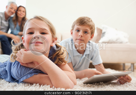 Happy siblings using a tablet computer with their parents on the stock photo, Happy siblings using a tablet computer with their parents on the background in a living room  by Wavebreak Media