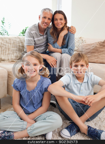 Portrait of a happy family posing stock photo, Portrait of a happy family posing in a living room by Wavebreak Media