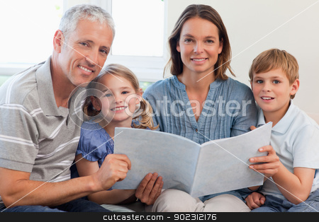 Happy family reading a book together stock photo, Happy family reading a book together in a living room by Wavebreak Media