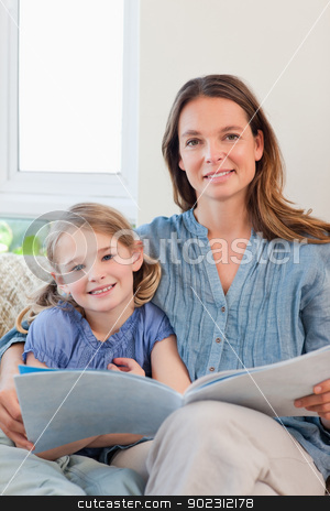 Portrait of a mother reading a book to her daughter stock photo, Portrait of a mother reading a book to her daughter in a living room by Wavebreak Media