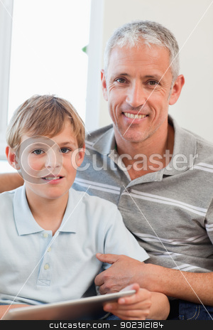 Portrait of a delighted father and his son using a tablet comput stock photo, Portrait of a delighted father and his son using a tablet computer in a living room by Wavebreak Media