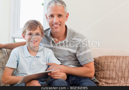 Smiling father and his son using a tablet computer stock photo, Smiling father and his son using a tablet computer in a living room by Wavebreak Media