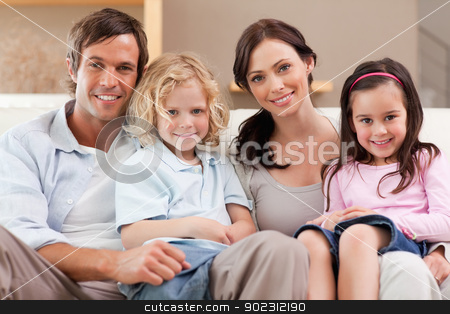 Happy family watching television together stock photo, Happy family watching television together in a living room by Wavebreak Media
