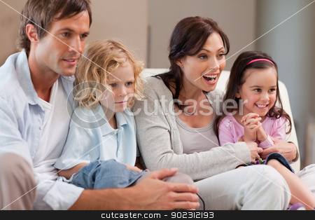 Cheerful family watching television together stock photo, Cheerful family watching television together in a living room by Wavebreak Media