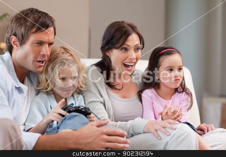Cheerful family playing video games together stock photo, Cheerful family playing video games together in a living room by Wavebreak Media