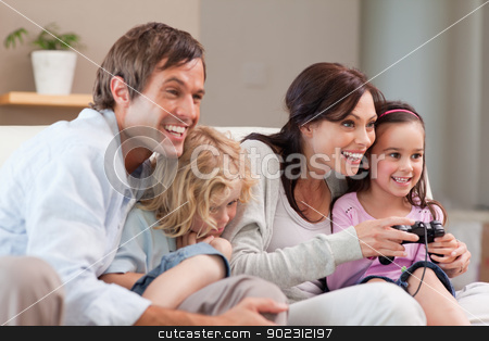 Delighted family playing video games together stock photo, Delighted family playing video games together in a living room by Wavebreak Media