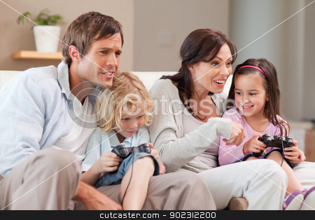 Competitive family playing video games together stock photo, Competitive family playing video games together in a living room by Wavebreak Media