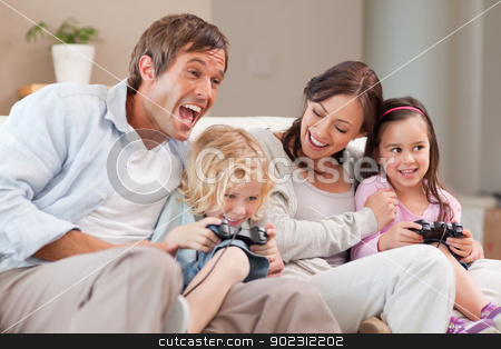Laughing family playing video games stock photo, Laughing family playing video games in a living room by Wavebreak Media