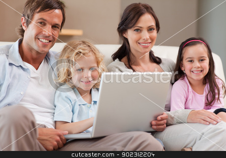 Calm family using a notebook stock photo, Calm family using a notebook in a living room by Wavebreak Media
