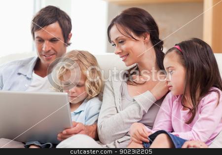 Serene family using a notebook stock photo, Serene family using a notebook in a living room by Wavebreak Media
