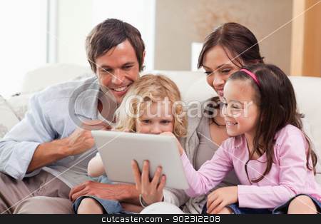 Delighted family using a tablet computer stock photo, Delighted family using a tablet computer in a living room by Wavebreak Media