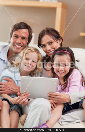 Portrait of a family using a tablet computer stock photo, Portrait of a family using a tablet computer in a living room by Wavebreak Media