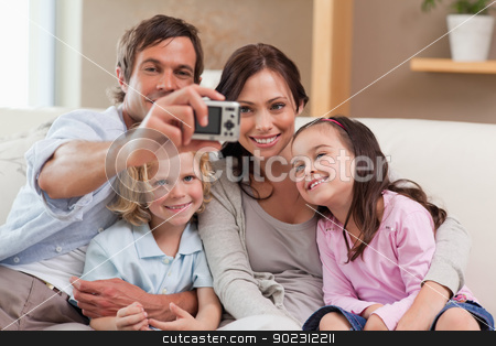 Father taking a picture of his family stock photo, Father taking a picture of his family in the living room by Wavebreak Media