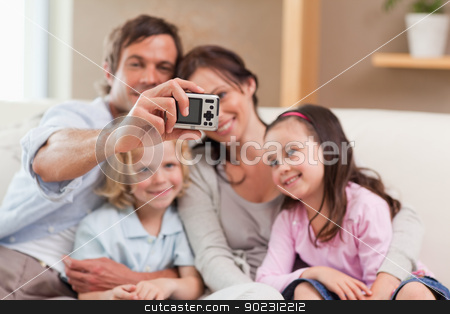 Happy father taking a picture of his family stock photo, Happy father taking a picture of his family in a living room by Wavebreak Media