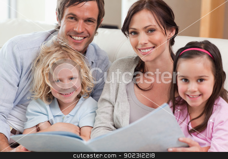 Close up of a family looking at a photo album stock photo, Close up of a family looking at a photo album in a living room by Wavebreak Media