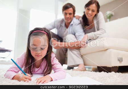 Little girl drawing with her parents in the background stock photo, Little girl drawing with her parents in the background while lying on a carpet by Wavebreak Media