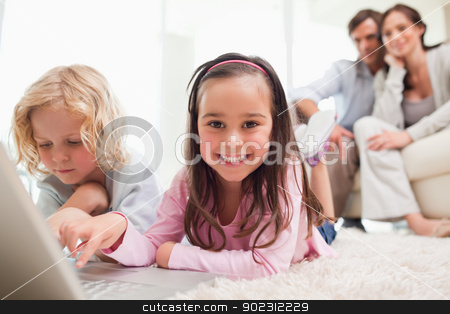 Siblings using a laptop while their parents are in the backgroun stock photo, Siblings using a laptop while their parents are in the background in a living room by Wavebreak Media