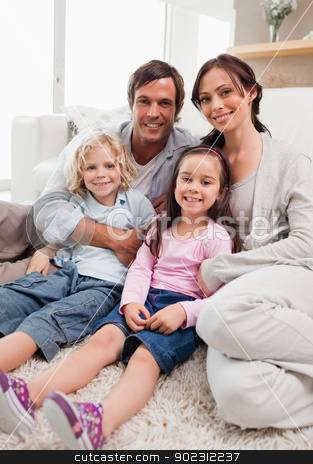 Portrait of a family relaxing in their living room stock photo, Portrait of a family relaxing in their living room while looking at the camera by Wavebreak Media