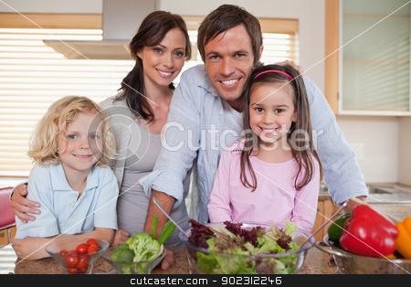 Family preparing a salad stock photo, Family preparing a salad in a kitchen by Wavebreak Media