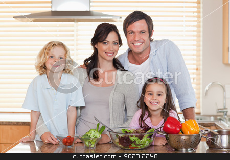 Family preparing a salad together stock photo, Family preparing a salad together in a kitchen by Wavebreak Media