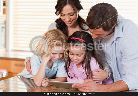 Happy family using a tablet computer together stock photo, Happy family using a tablet computer together in a kitchen by Wavebreak Media