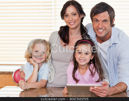 Smiling family using a tablet computer together stock photo, Smiling family using a tablet computer together in a kitchen by Wavebreak Media