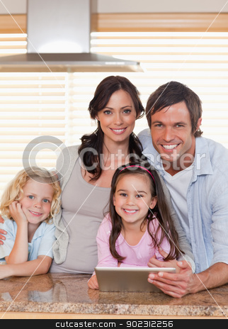 Portrait of a smiling family using a tablet computer together stock photo, Portrait of a smiling family using a tablet computer together in a kitchen by Wavebreak Media