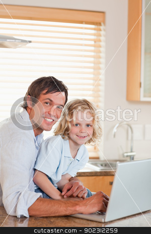 Portrait of a boy and his father using a notebook together stock photo, Portrait of a boy and his father using a notebook together in a kitchen by Wavebreak Media