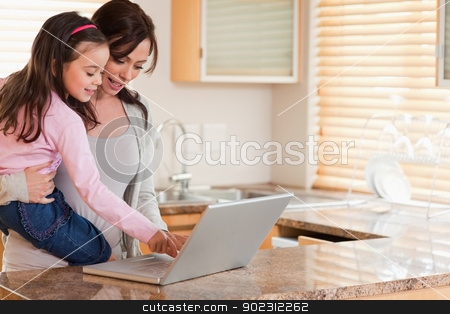 Girl and her mother using a laptop stock photo, Girl and her mother using a laptop in a kitchen by Wavebreak Media