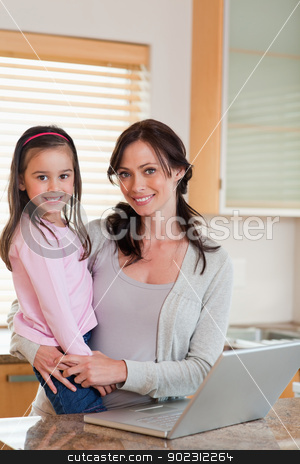Portrait of a girl and her mother using a notebook stock photo, Portrait of a girl and her mother using a notebook in a kitchen by Wavebreak Media