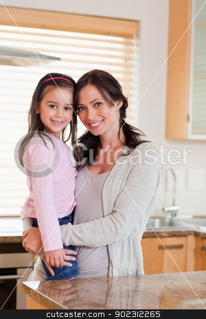 Portrait of a girl and her mother stock photo, Portrait of a girl and her mother in a kitchen by Wavebreak Media
