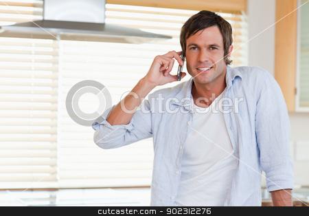 Happy man making a phone call stock photo, Happy man making a phone call in his kitchen by Wavebreak Media