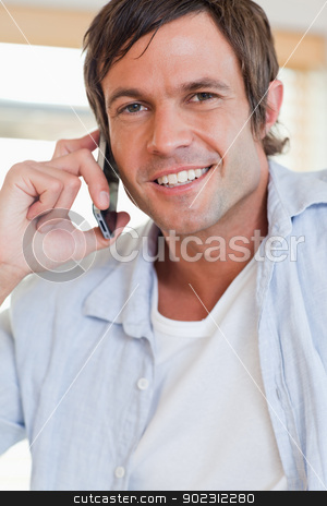 Portrait of an attractive man making a phone call stock photo, Portrait of an attractive man making a phone call in a kitchen by Wavebreak Media