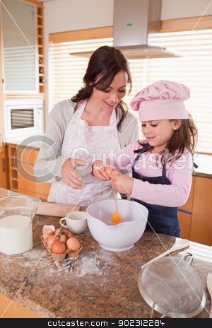 Portrait of a mother and her happy daughter baking stock photo, Portrait of a mother and her happy daughter baking in a kitchen by Wavebreak Media