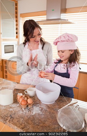 Portrait of a mother teaching her daughter how to bake stock photo, Portrait of a mother teaching her daughter how to bake in a kitchen by Wavebreak Media